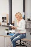 Lächelnde Büro-Frau auf Tabellen-Leseanmerkungen Stockfotografie