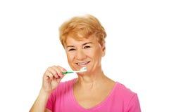 Lächelnde bürstende Zähne der älteren Frau Lizenzfreie Stockfotos