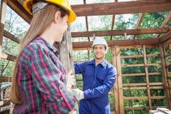 Lächelnde Bauarbeiter, die Leiter an halten Stockbild