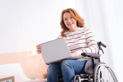 Lächelnde behinderte Frau, die an ihrem Laptop arbeitet Lizenzfreies Stockfoto