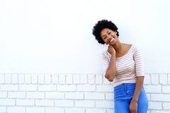 Lächelnde bereitstehende weiße Backsteinmauer der afrikanischen Frau Stockbild