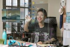 Lächelnde Berufs- Frau, die ein futuristisches Tischplatten-Comput laufen lässt stockfotografie