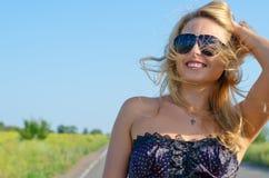 Lächelnde bloande Frau in den Sonnenbrillen stockbild