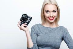 Lächelnde blond-haarige Frau, die mit Kamera aufwirft Stockbilder