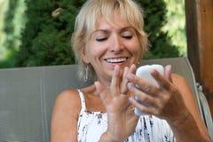 Lächelnde blonde ältere Frau steuert ihren Smartphone Lizenzfreie Stockfotografie