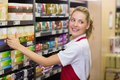 Lächelnde blonde Arbeitskraft, die ein Produkt im Regal nimmt Lizenzfreie Stockfotos