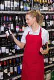 Lächelnde blonde Arbeitskraft, die eine Weinflasche betrachtet Stockbild