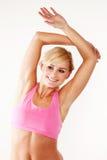 Lächelnde blonde ausarbeitende Frau Stockfoto
