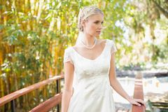 Lächelnde blonde Braut in der Perlenhalskette, die auf einer Brücke steht Lizenzfreies Stockfoto
