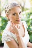 Lächelnde blonde Braut in der Perlenhalskette, die ihr Gesicht berührt Lizenzfreies Stockfoto