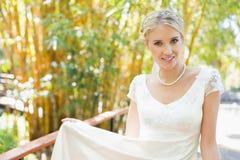 Lächelnde blonde Braut in der Perlenhalskette, die Kamera betrachtet Stockbild