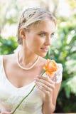 Lächelnde blonde Braut in der Perlenhalskette, die Orange hält, stieg Lizenzfreies Stockfoto