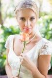 Lächelnde blonde Braut in der Perlenhalskettenholding stieg Lizenzfreie Stockfotografie