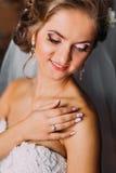Lächelnde blonde Braut in der Schleier- und Perlenhalskette, die zuhause ihre Schulter berührt Stockfoto