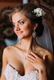 Lächelnde blonde Braut in der Schleier- und Perlenhalskette, die zuhause ihren Hals berührt Lizenzfreies Stockbild