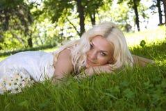 Lächelnde blonde Braut, die auf Gras liegt Lizenzfreie Stockfotos
