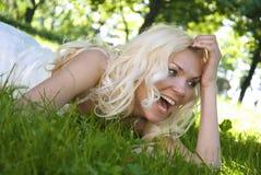 Lächelnde blonde Braut, die auf Gras liegt Stockfoto