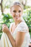 Lächelnde blonde Braut, die ihr Kleid betrachtet Kamera hält Lizenzfreie Stockbilder