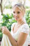 Lächelnde blonde Braut, die ihr Kleid hält Stockfoto