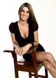 Lächelnde blonde Dame, die auf einem Stuhl sitzt Lizenzfreies Stockbild