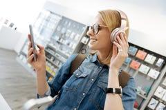 Lächelnde blonde Dame, die Modellkopfhörer am Shop verwendet Lizenzfreie Stockbilder
