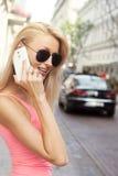 Lächelnde blonde Dame, die telefonisch spricht Lizenzfreie Stockfotos