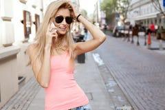 Lächelnde blonde Dame, die telefonisch spricht Lizenzfreie Stockfotografie