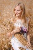 Lächelnde blonde Dame mit Garbe Weizen haftet Stockfotos