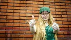 Lächelnde blonde darstellende Daumen oben Lizenzfreie Stockfotos