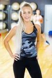 Lächelnde blonde Eignungsfrau in der Trainingsausstattung an der Turnhalle Lizenzfreie Stockbilder