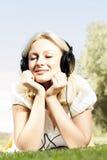 Lächelnde blonde entspannende Frau des Glückes Stockfoto