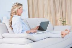 Lächelnde blonde Entspannung auf Couch mit ihrem Laptop Stockfotos
