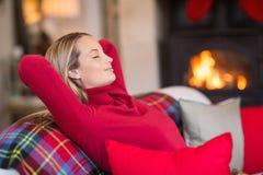 Lächelnde blonde Entspannung auf der Couch am Weihnachten Lizenzfreie Stockfotografie