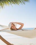 Lächelnde blonde Entspannung auf Hängematte Stockfoto