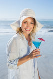 Lächelnde blonde Entspannung durch das Meer, das Cocktail hält Lizenzfreies Stockfoto