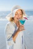 Lächelnde blonde Entspannung durch das Seenippende Cocktail Lizenzfreie Stockbilder