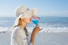Lächelnde blonde Entspannung durch das Seenippende Cocktail Lizenzfreie Stockfotografie