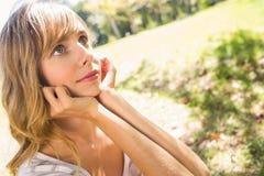 Lächelnde blonde Entspannung im Gras Stockfoto
