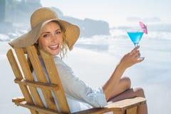 Lächelnde blonde Entspannung im Klappstuhl durch das Meer, das Cocktail hält Stockfotografie