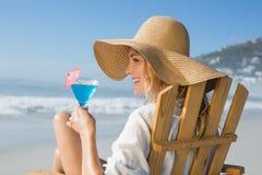 Lächelnde blonde Entspannung im Klappstuhl durch das Meer, das Cocktail hält Lizenzfreie Stockbilder