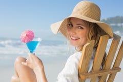 Lächelnde blonde Entspannung im Klappstuhl durch das Meer, das Cocktail hält Lizenzfreie Stockfotografie
