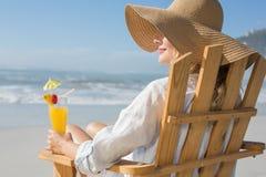 Lächelnde blonde Entspannung im Klappstuhl durch das Meer, das Cocktail hält Lizenzfreies Stockbild