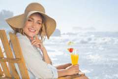 Lächelnde blonde Entspannung im Klappstuhl durch das Meer, das Cocktail hält Stockfotos