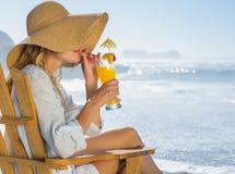 Lächelnde blonde Entspannung im Klappstuhl durch das Seenippende Cocktail Stockbild