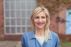 Lächelnde blonde erwachsene Frau außerhalb des Gebäudes Lizenzfreie Stockfotografie