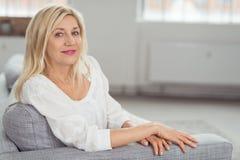 Lächelnde blonde erwachsene Frau, die auf Gray Couch sitzt Stockbild