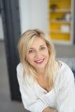 Lächelnde blonde erwachsene Frau, welche die Kamera betrachtet Lizenzfreie Stockbilder
