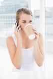 Lächelnde blonde Frau auf dem trinkenden Kaffee des Telefons Lizenzfreies Stockbild