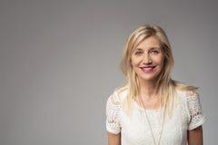 Lächelnde blonde Frau auf Grau mit Kopien-Raum Stockfoto