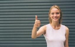 Lächelnde blonde Frau auf grauem Hintergrund Recht blondes Mädchen, das mit dem Daumen oben vor der Kamera, positiv lächelt Lizenzfreies Stockfoto